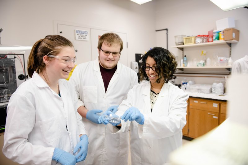 Two students working with a professor in a lab.